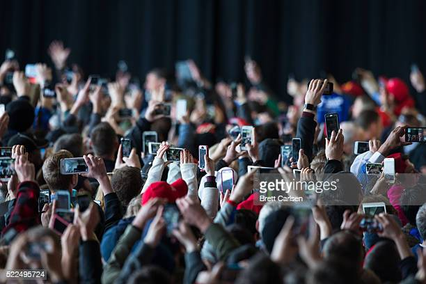 Crowds of supporters photograph Donald Trump as he walks on stage to speak at a rally for his presidential campaign on April 10 2016 in Rochester New...