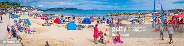 Crowds of tourists enjoying ocean beach Lyme Regis Dorset UK
