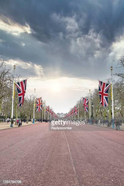 ユニオンジャックに沿って並ぶ観光客の群衆は、脅かす暗い空の下でバッキンガム宮殿、ロンドン、英国へのラインをリードする強い視点でモールの景色を飾りました - ロンドン ザ・マル ストックフォトと画像