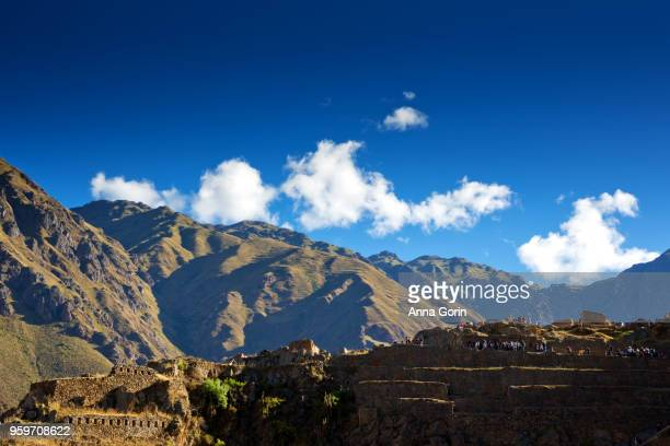 Crowds of tourists on Inca terraces of Ollantaytambo in Sacred Valley of Peru, mountains in background