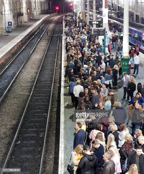 Crowds of train passengers in the UK waiting on the station platform