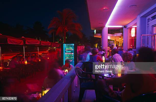 Crowds of visitors and locals gather on the terrace of an Ocean Drive cafe in Miami Beach It is early evening and we see the blurred people moving...