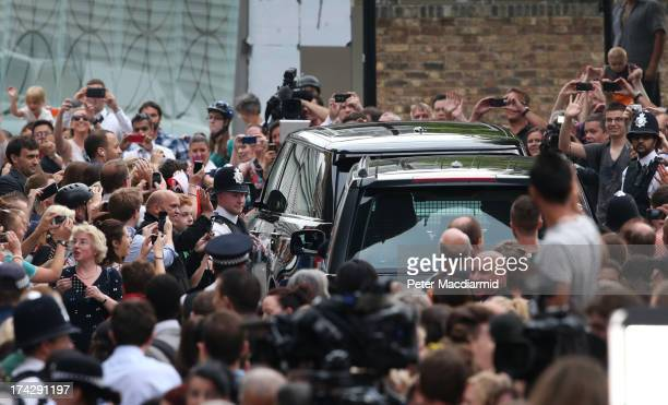 Crowds of well wishers take photographs as Prince William Duke of Cambridge and Catherine Duchess of Cambridge depart The Lindo Wing with their...