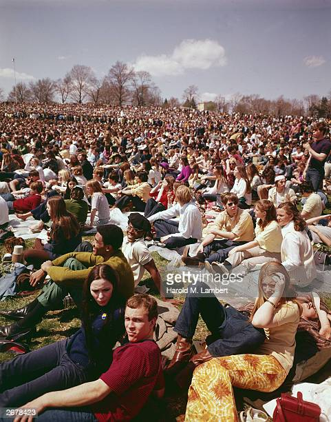 Crowds of young men and women sit in a park during celebrations for Earth Day circa 1970