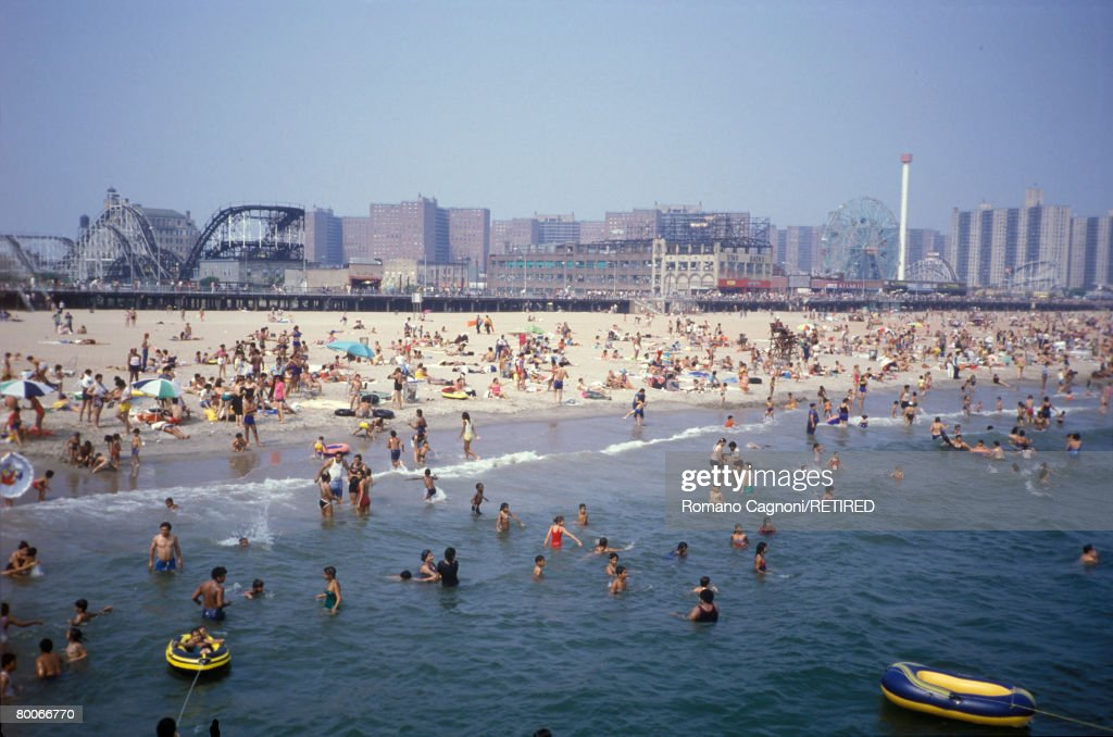 Crowds on Coney Island beach, New York, with amusement parks in the background, circa 1990.