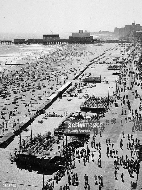 Crowds on the beach and the boardwalk in Atlantic City New Jersey circa 1950