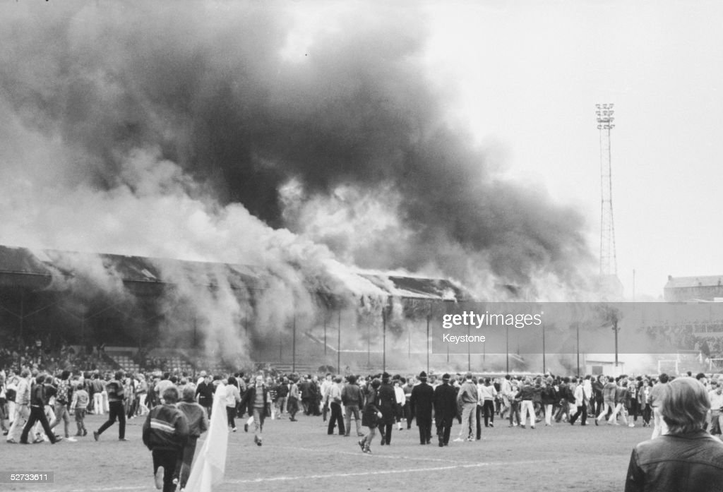Crowds on the pitch at Bradford City's Valley Parade stadium after the stand caught fire. In less than five minutes the whole Main Stand was ablaze causing the deaths of 56 supporters in one of the worst incidents in British football, 11th May 1985.