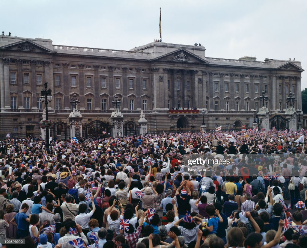 Crowds outside Buckingham Palace on the day of the wedding of Prince Charles and Lady Diana Spencer, London, 29th July 1981. The couple and their family are posing on the balcony.