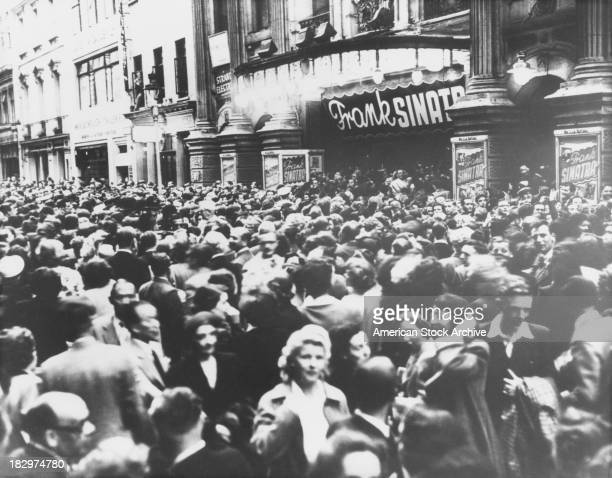 Crowds outside the London Palladium theatre, which is advertising an appearance by American actor and singer Frank Sinatra, circa 1950.