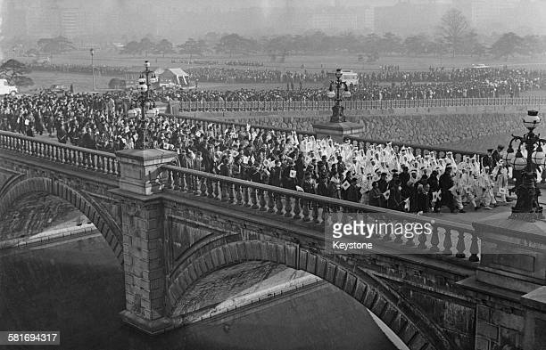 Crowds pour across the bridge into the Imperial Palace park Tokyo Japan during the New Year celebrations January 1963