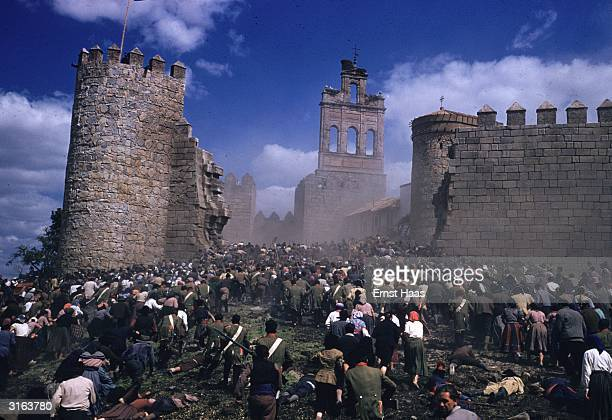 Crowds pour through a breach in the wall of a citadel in a scene from the United Artists production of 'The Pride and The Passion' directed by...