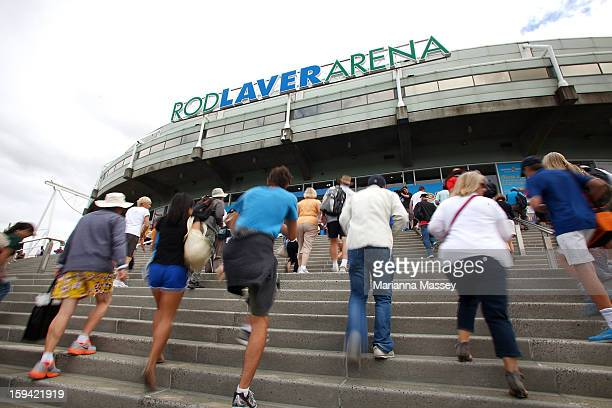 Crowds rush through the gates as they are opened for the start of day one of the 2013 Australian Open at Melbourne Park on January 14 2013 in...