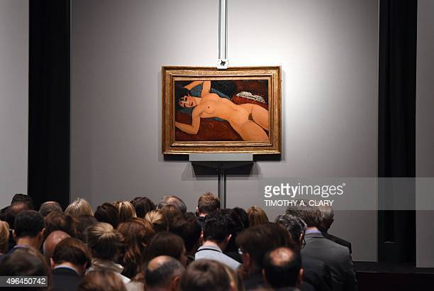 Crowds sit in front of Amedeo Modigliani's 'Nu couche' during the 'Artist Muse A Curated Evening Sale' November 9 2015 at Christie's New York...