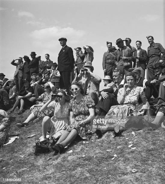 Crowds sit on the grass to watch the wartime New Derby run at Newmarket racecourse in Suffolk 18th June 1941 Owen Tudor won the race ridden by Willie...