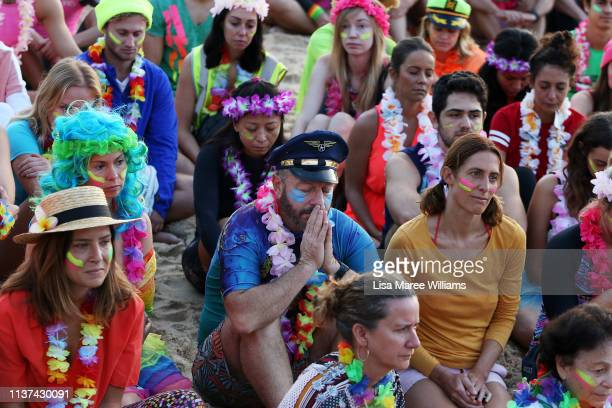 Crowds sits for a moments silence in solidarity with OneWave at sunrise on Bondi Beach on March 22 2019 in Sydney Australia Surfers gather to...