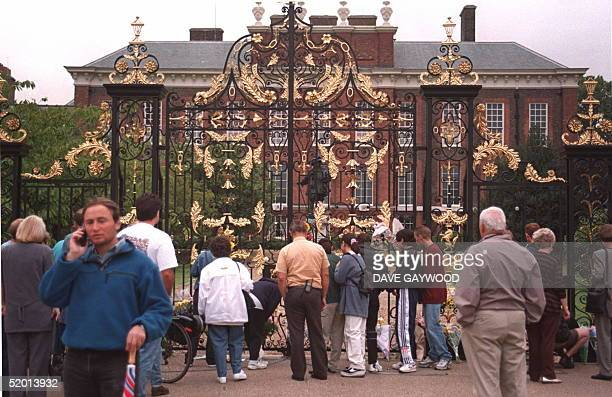 Crowds stand in silence outside the home of the Princess of Wales Kensington Palace after it was announced that she had died early today after a...