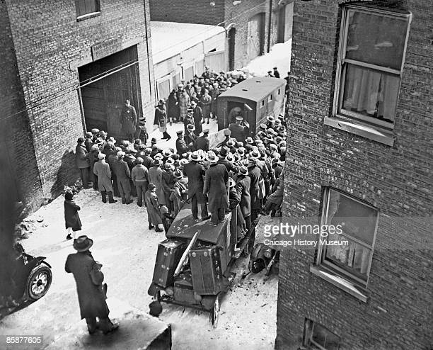Crowds stand outside a garage at 2122 North Clark Street in the Lake View community area of Chicago Illinois as men wearing uniforms move a stretcher...