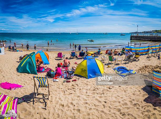 Crowds sunbathing on sandy ocean beach with colourful tents England