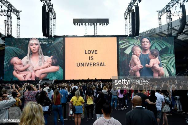 Crowds take photos with their mobile phones as images of Beyonce and JayZ are projected before they appear to perform on stage during the On the Run...