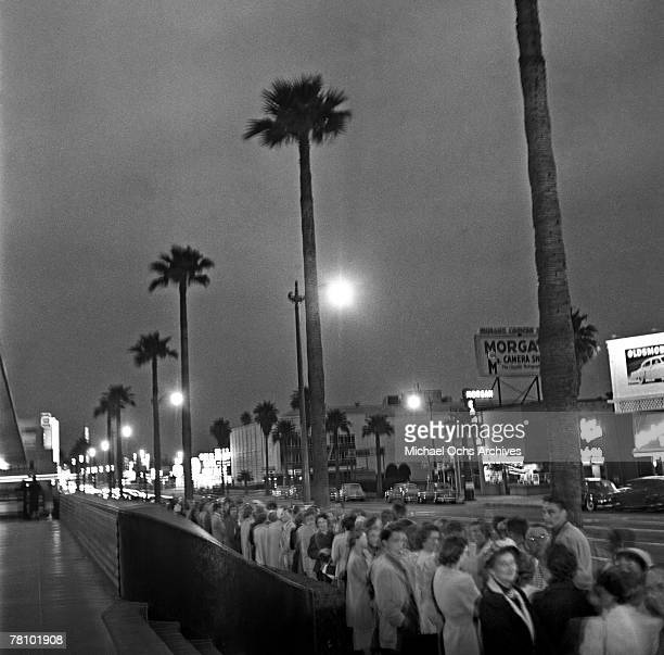 Crowds wait outside a movie premiere on Hollywood Boulevard at night on June 7 1951 in Los Angeles California