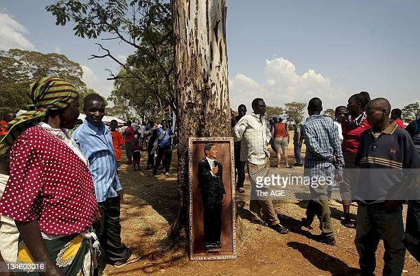 Crowds walk past a wooden relief of Barak Obama at the Senator Obama primary school in Kogelo Kenya Thousands gathered before a small tv and another...