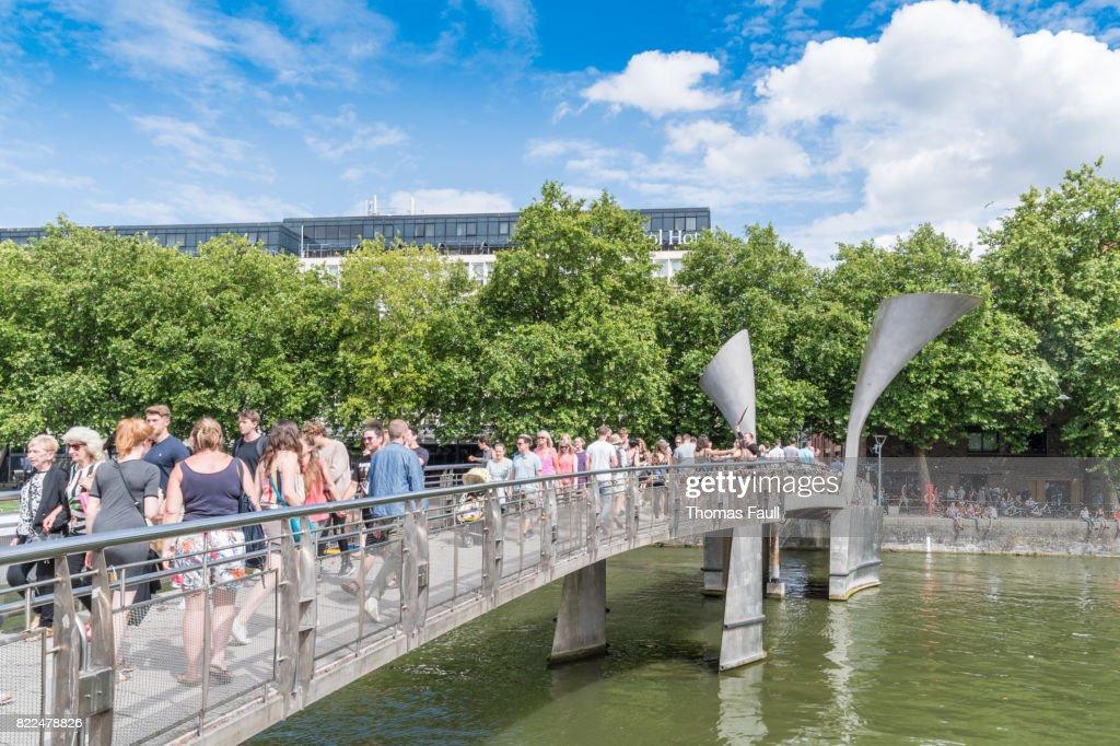 Crowds walking over Pero's Bridge in Bristol : Stock Photo