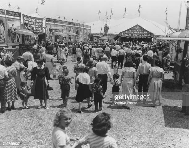 Crowds walking past various sideshows on their way to ther main entrance of the Ringling Bros and Barnum Bailey Circus USA 1949 Among the sideshows...