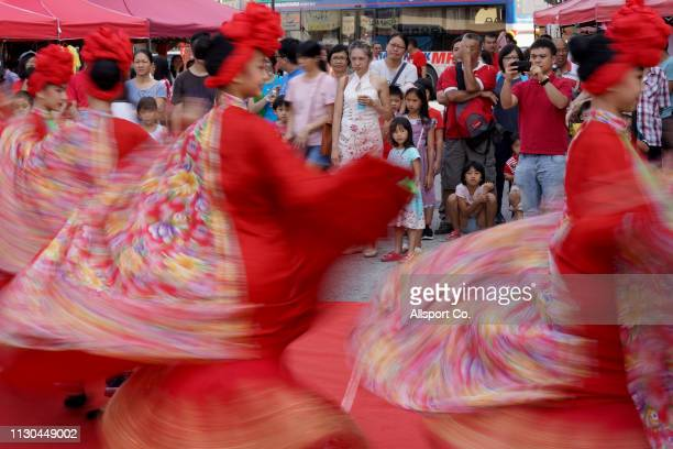 Crowds watch as ethnic Chinese girls perform a traditional Chinese dance during a Chinese New Year day of 13th celebration at the Tin Hong Si temple...
