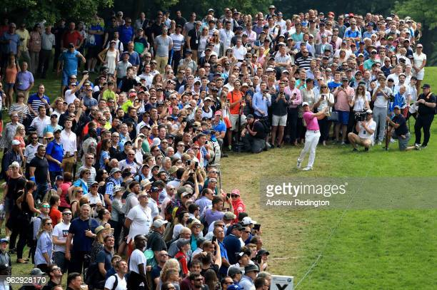 Crowds watch as Rory McIlroy of Northern Ireland plays his second shot on the 1st hole during day four and the final round of the BMW PGA...