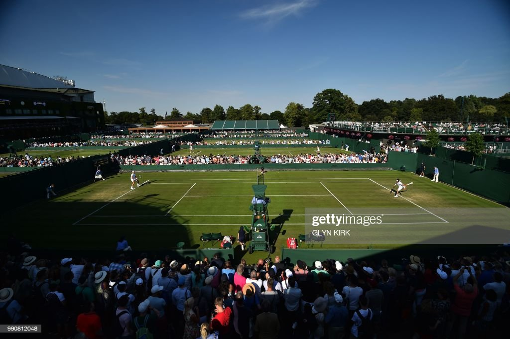 Crowds watch as Spain's David Ferrer (R) serves against Russia's Karen Khachanov during their men's singles first round match on the second day of the 2018 Wimbledon Championships at The All England Lawn Tennis Club in Wimbledon, southwest London, on July 3, 2018. (Photo by Glyn KIRK / AFP) / RESTRICTED