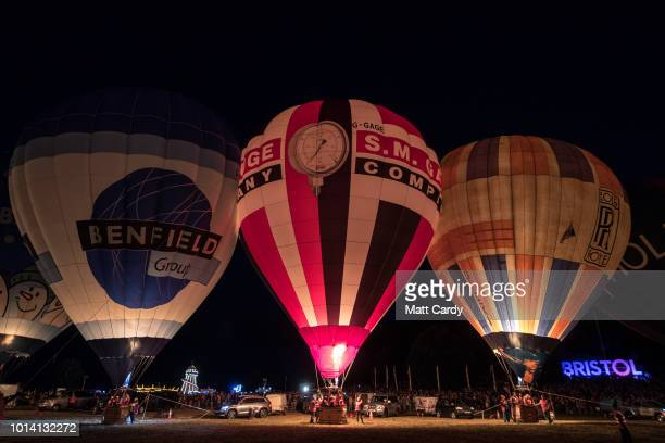 Crowds watch as tethered balloons are illuminated by their burners during the night glow evening event on the first day of the Bristol International...