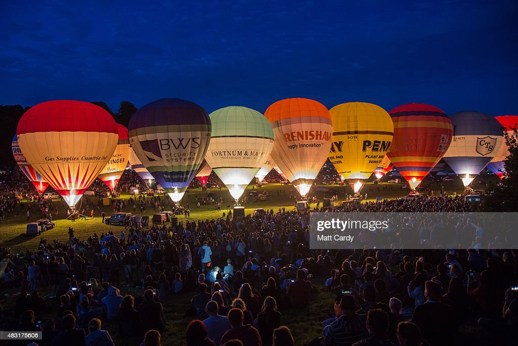 Crowds watch as tethered balloons are illuminated by their burners during the night glow evening event on the first day of the Bristol International Balloon Fiesta at the Ashton Court estate on August 6, 2015 in Bristol, England. Now in its 37th year, the Bristol International Balloon Fiesta is Europe's largest annual hot air balloon event in the city that is seen by many balloonists as the home of modern ballooning.