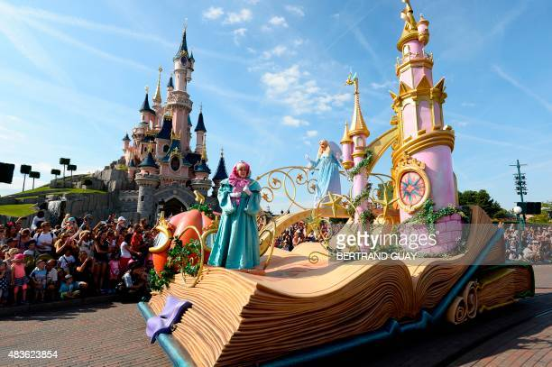 Crowds watch as the Cinderella float passes by during the Main Street Parade at Disneyland Paris in MarnelaVallee on August 6 2015 AFP PHOTO /...