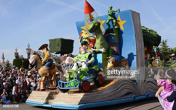 Crowds watch as the Toy Story float rides past during the Main Street Parade at Disneyland Paris in MarnelaVallee on August 6 2015 AFP PHOTO /...