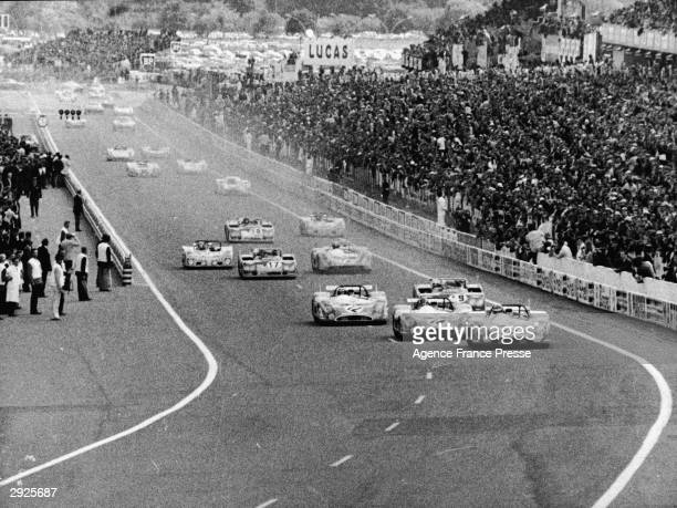 Crowds watch cars on the race track at the 24 Hour Le Mans competition France June 10 1972