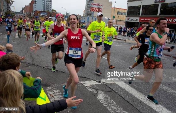 Crowds watch New York City marathon runners as they race up 4th Avenue on November 5 2017 in the Gowanus neighborhood of Brooklyn New York