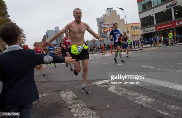 Crowds watch New York City marathon runners as they race up 4th Avenue on November 5 2017 in the Gowanus neighborhood of Brooklyn New York
