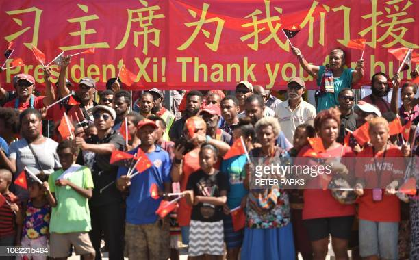 Crowds wave as China's President Xi Jinping arrives for his visit to the Butuka Academy school in Port Moresby on November 16 ahead of the...