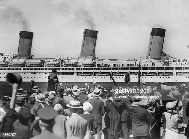 Crowds wave as the White Star liner Majestic leaves her pier, loaded with tourists bound for Europe.
