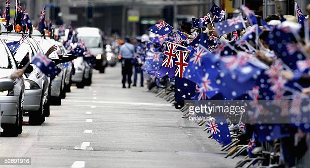 Crowds wave flags and banners as war veterans pass by in taxis during the Anzac Day parade April 25 2005 in Sydney Australia Australians and New...