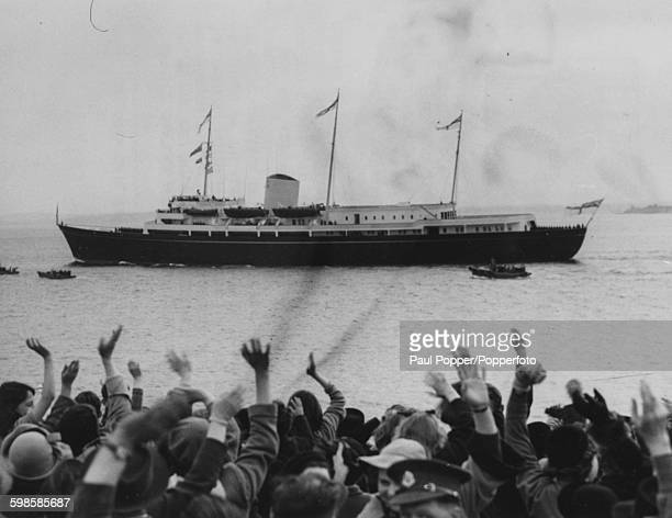 Crowds wave from shore as the Royal Yacht Britannia departs from Portsmouth with the royal children Princess Anne and Prince Charles aboard destined...