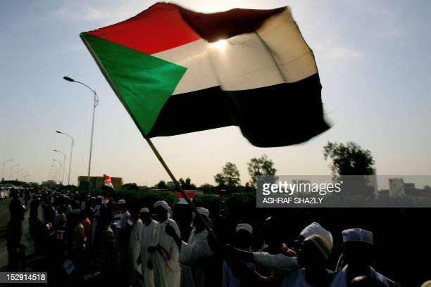 Crowds wave the Sudanese flag as they greet President Omar alBashir outside Khartoum airport on September 28 2012 upon his return from Addis Ababa...