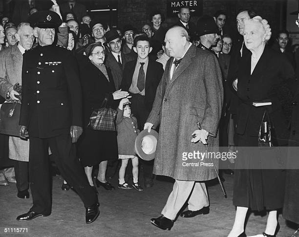 Crowds welcome British statesman Winston Churchill and his wife Clementine as they arrive at King's Cross station 9th October 1952 The couple are...