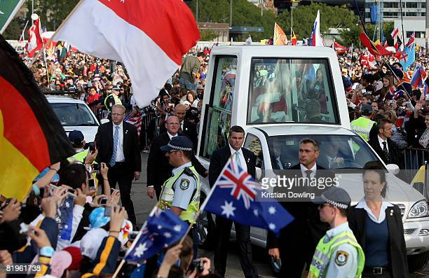 Crowds welcome the Holy Father Pope Benedict XVI as he arrives in his Pope Mobile at the Papal Welcome Ceremony at Barangaroo on Sydney Harbour on...