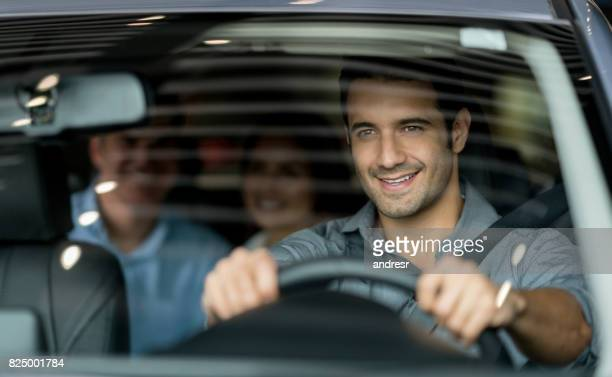 crowdsource taxi driver driving a couple of customers - driver stock pictures, royalty-free photos & images