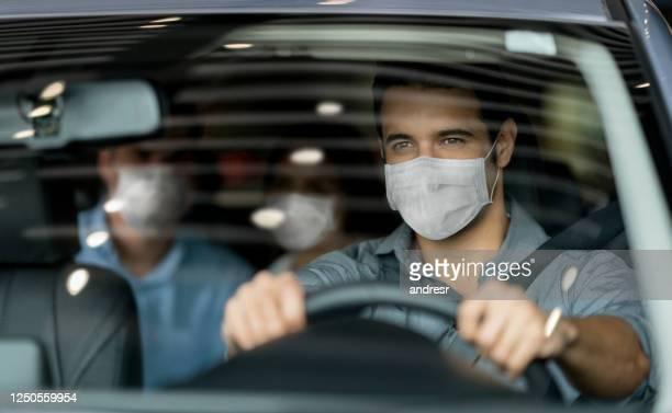 顧客のカップルを運転しながら、フェイスマスクを身に着けているクラウドソーシングタクシー運転手 - 試運転 ストックフォトと画像