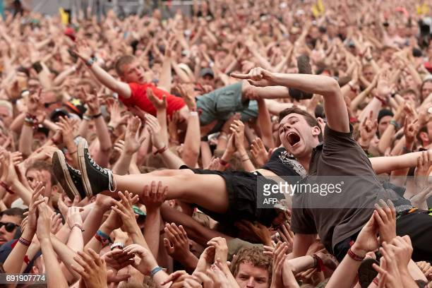 TOPSHOT Crowdsurfers are pictured during a performance of 'Broilers' group at the 'Rock am Ring' music festival on June 3 2017 in Nuerburg Germany's...