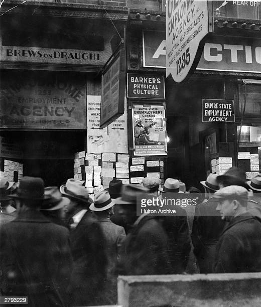 A crowed of unemployed men gather in the rain in front of a row of employment agencies on Sixth Avenue during the Great Depression New York City 1931