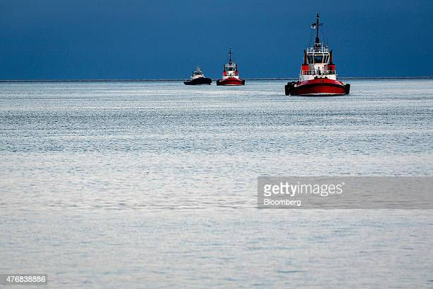 Crowley tug boats return to the harbor after guiding container ships out of the channel at the Port of Los Angeles in Los Angeles California US on...