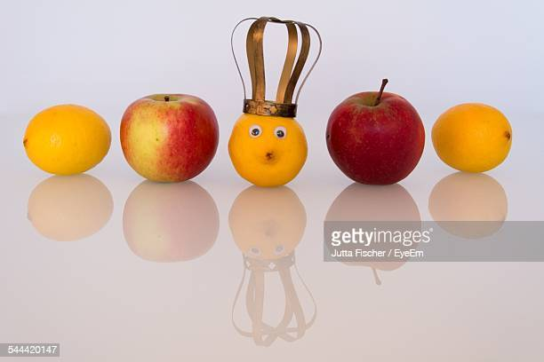 crown on orange amidst fruits on white background - crown close up stock pictures, royalty-free photos & images